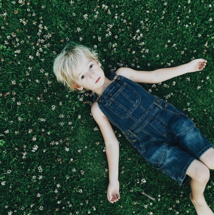 portrait of boy laying in the grass by ashley jenny, the stork and the beanstalk, for childhood unplugged instagram