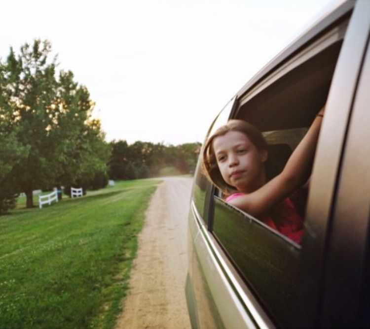 girl with her head in the breeze out of the car window for childhood unplugged hashtag on instagram #cu_travel